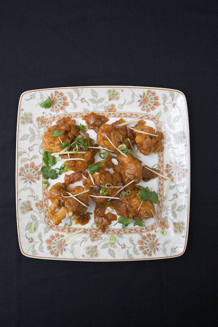 Gobi Manchurian; Fried Cauliflower; On a Plate; Black Background