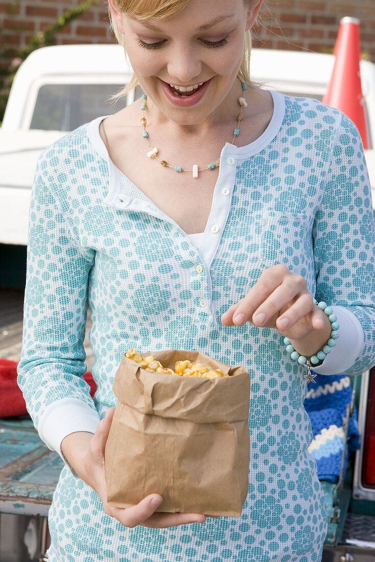 Woman Eating Caramel Corn from a Paper Bag