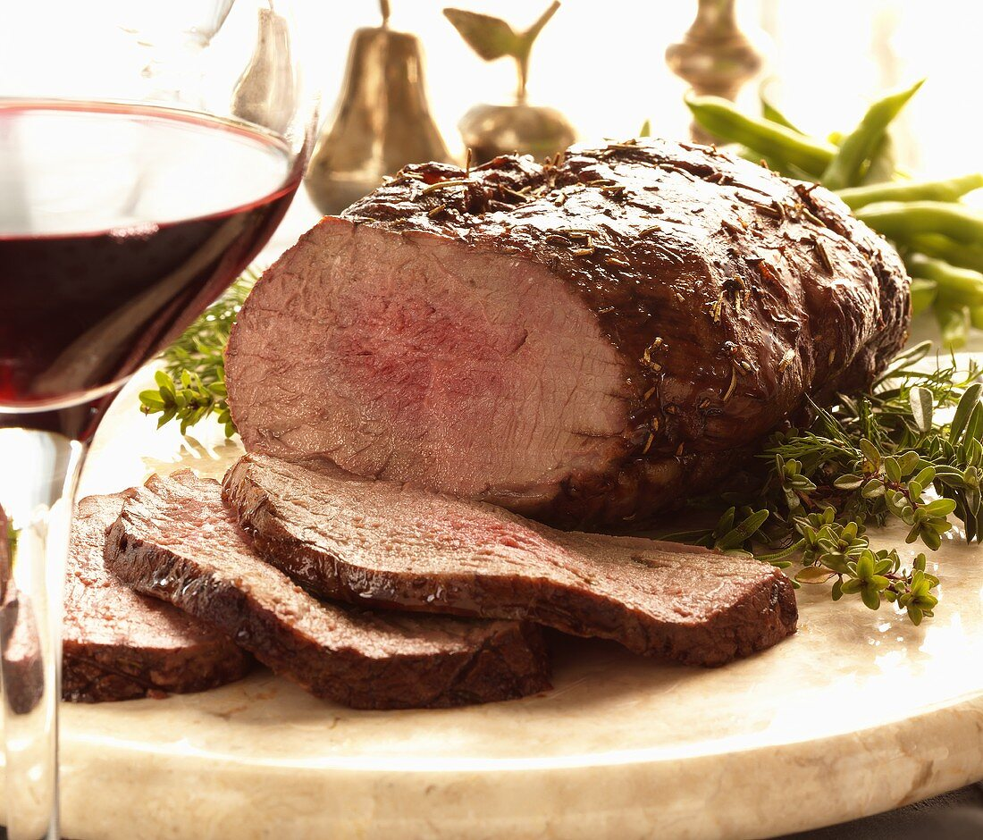 Sliced Beef Roast on Wooden Board with Herbs and a Glass of Red Wine
