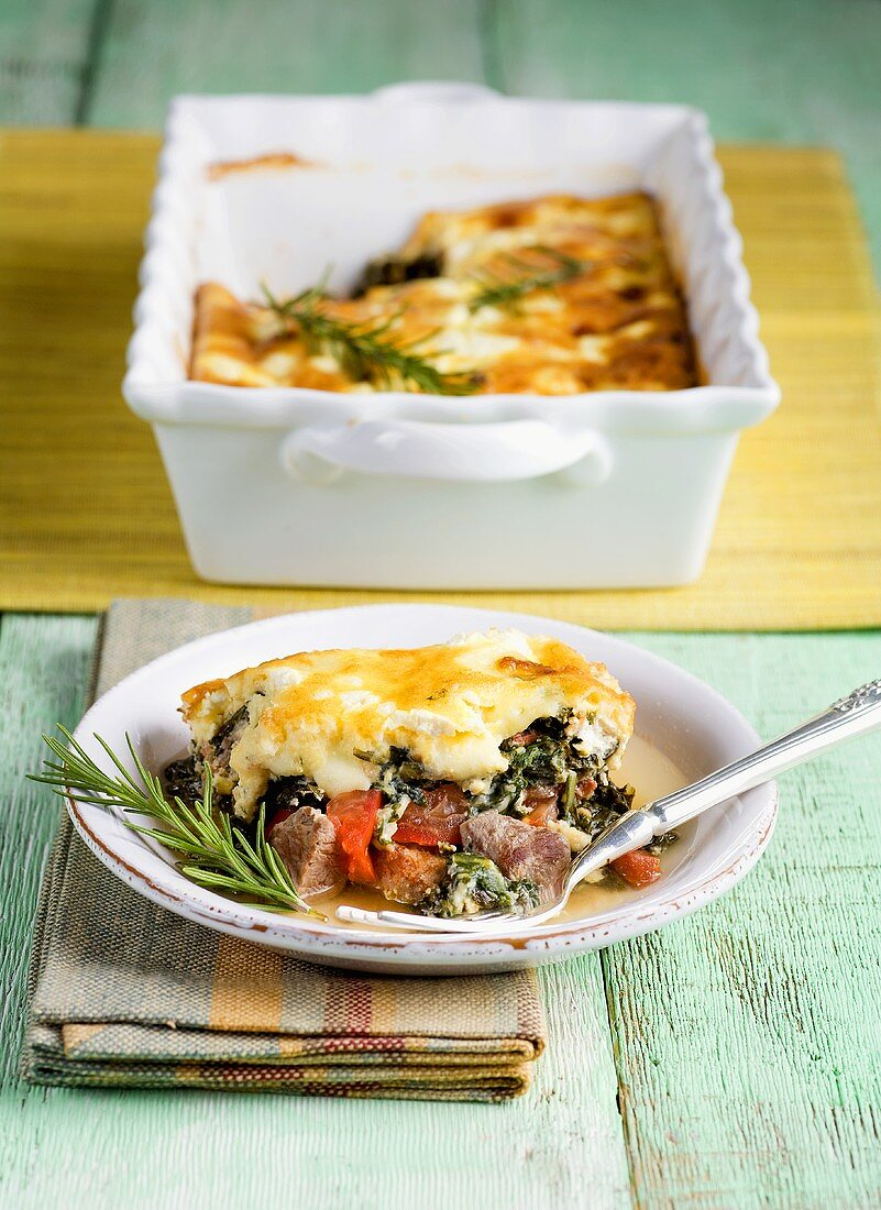 Serving of Lamb and Dandelion Casserole on a Plate, Baking Dish