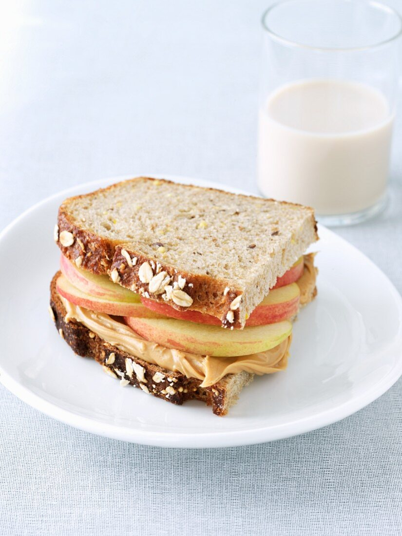 Peanut Butter and Apple Sandwich on Whole Grain Bread; Glass of Rice Milk