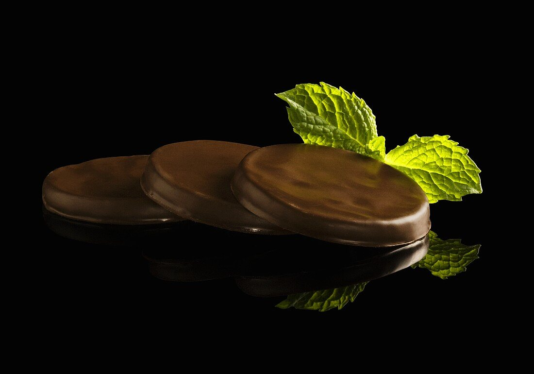 Three Chocolate Mint Cookies with Fresh Mint on Black Background