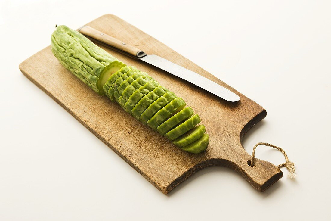 Partially Sliced Bitter Melon on a Cutting Board