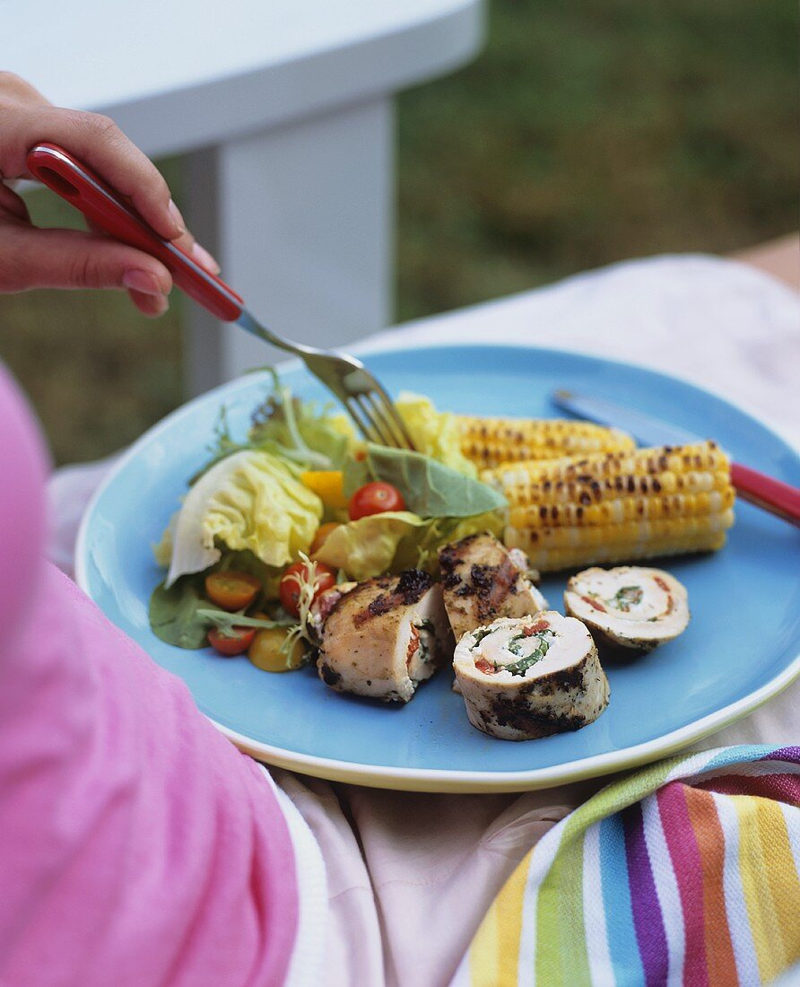 Woman Sitting with Barbecued Diner on Lap, Pesto Stuffed Chicken, Salad and Corn