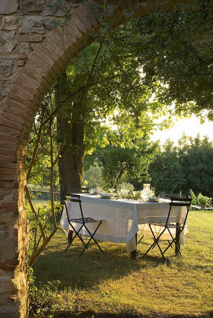 A view through an archway onto a table laid in a garden