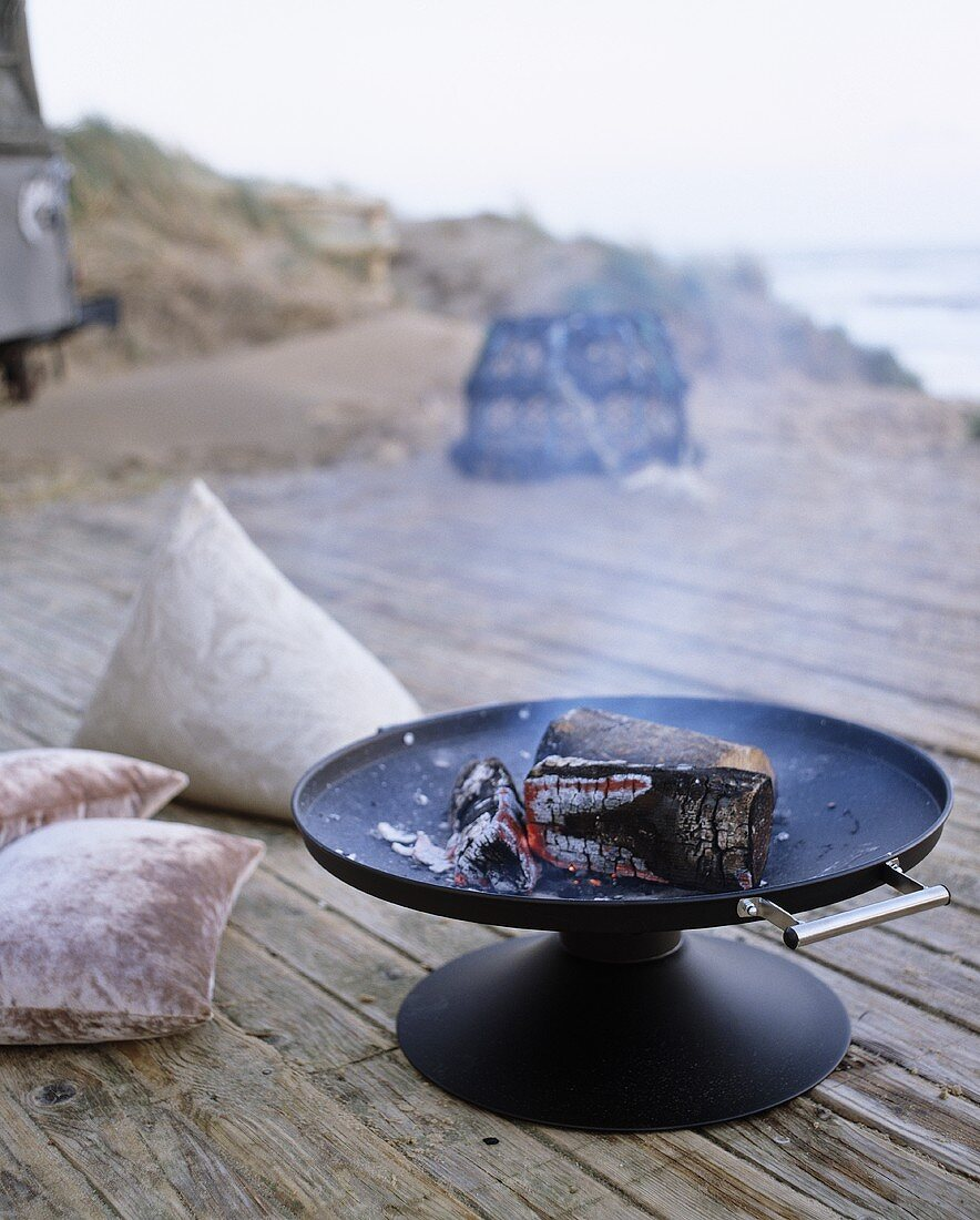 Glowing embers in a fire bowl on a terrace with a sea view