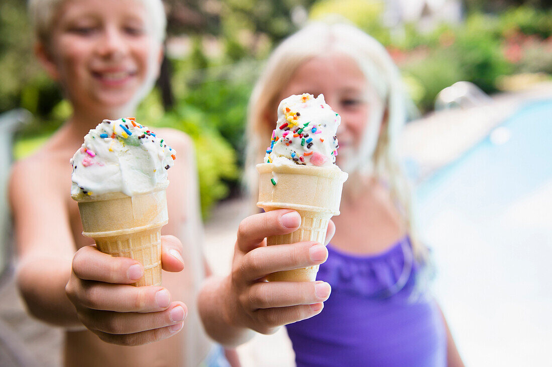 Caucasian children eating ice cream near swimming pool, Huntington Station, New York, USA