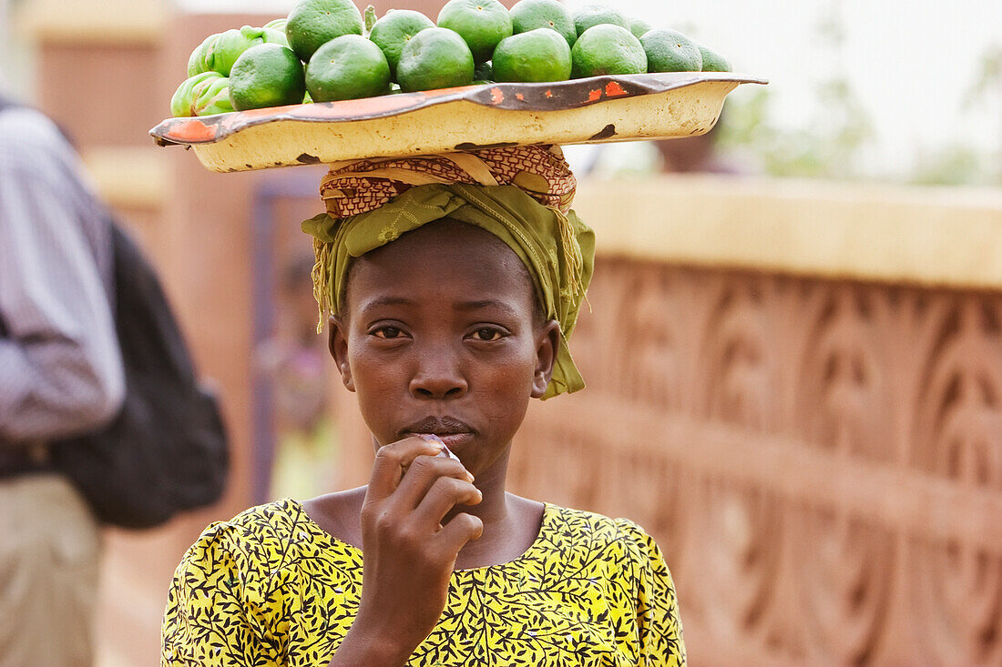 Girl carrying fruits on her head in Segou, Mali