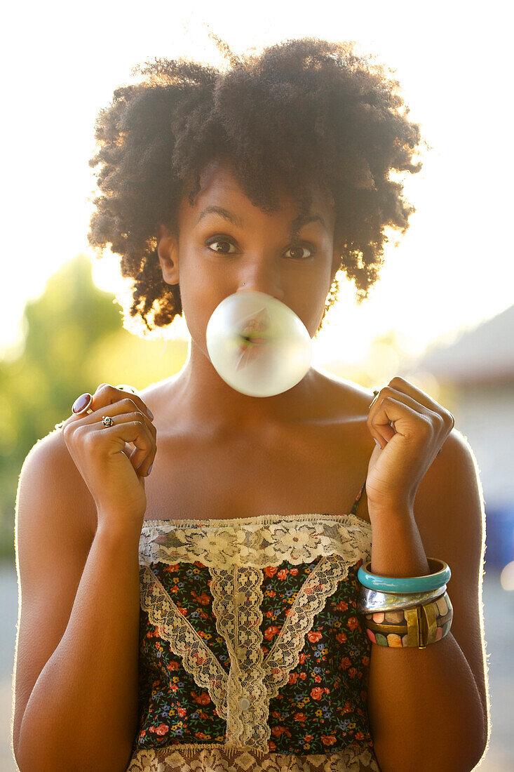 Woman blowing bubble gum bubble outdoors