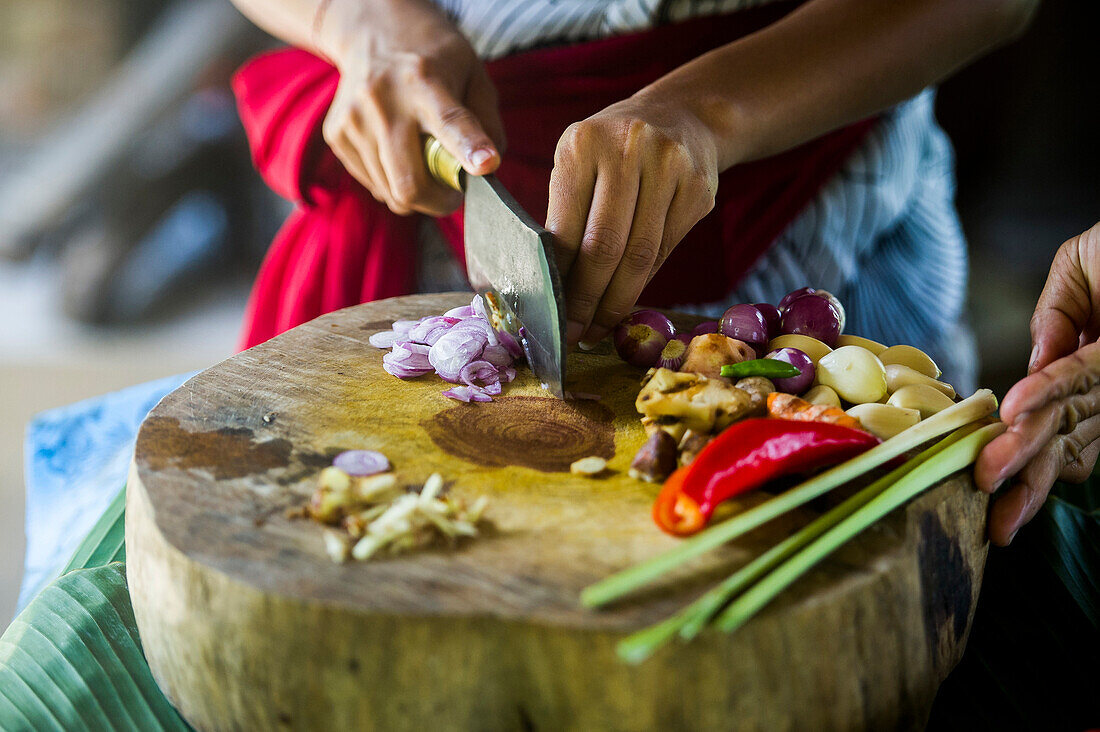 Close up of chefs chopping vegetables on cutting board