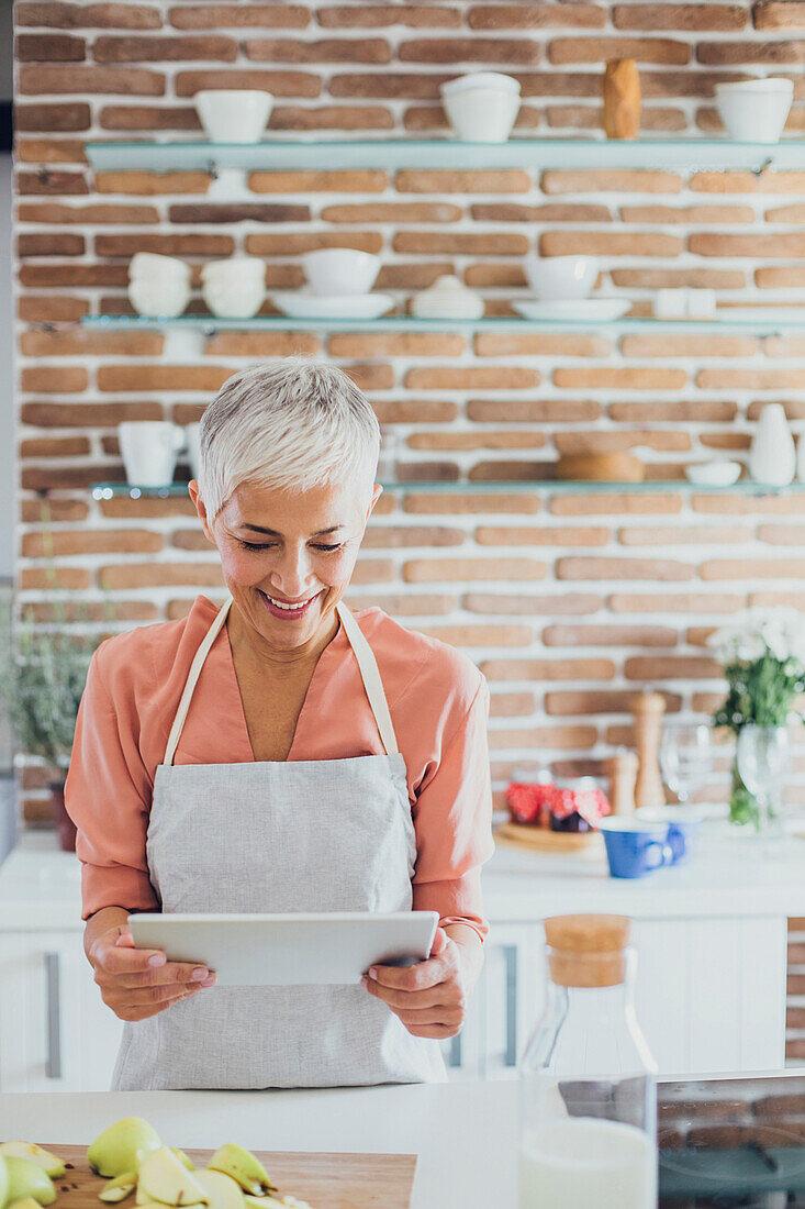 Older Caucasian woman using digital tablet in kitchen