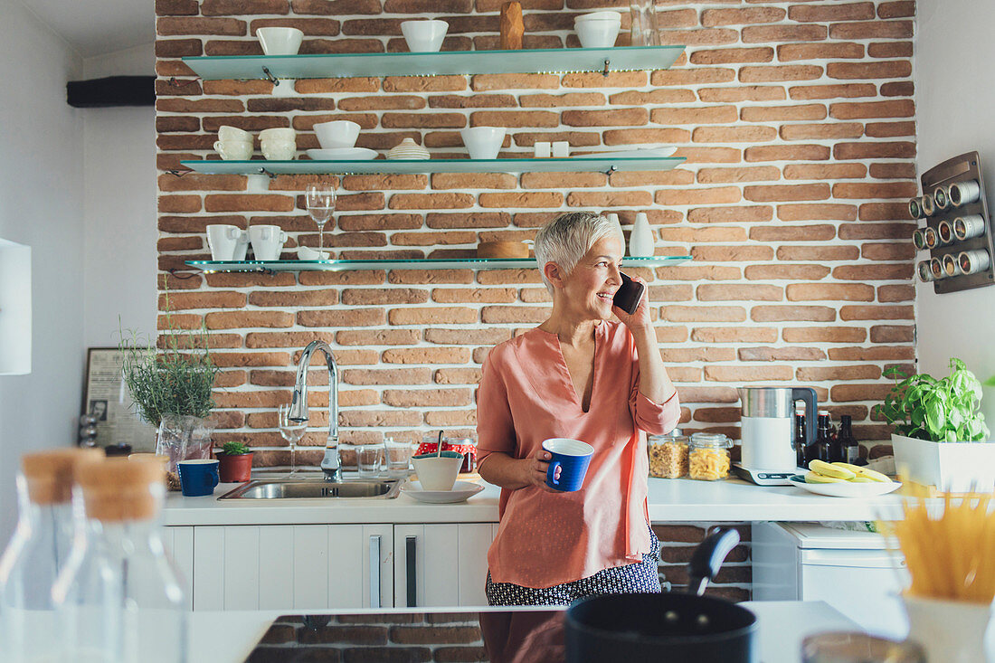 Older Caucasian woman talking on cell phone in kitchen