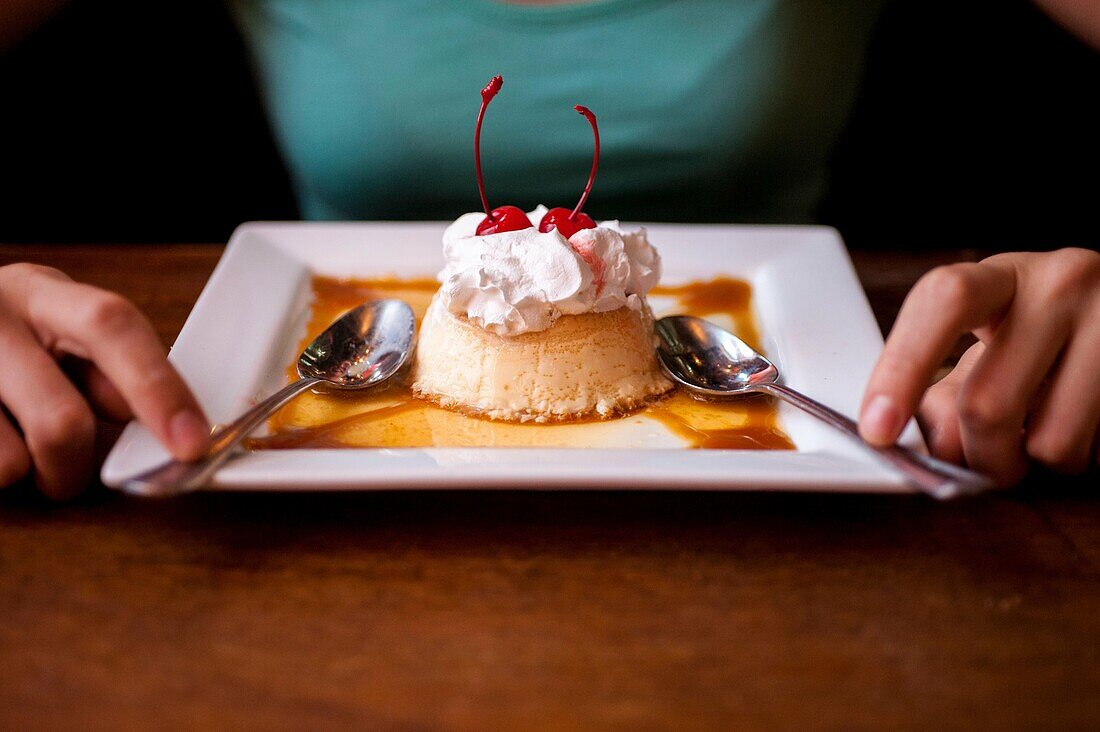 A flan dessert on a plate in a restaurant win a woman´s hands next to the plate.