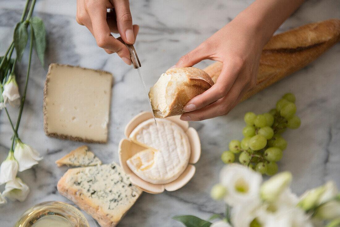 Hispanic woman spreading cheese on bread