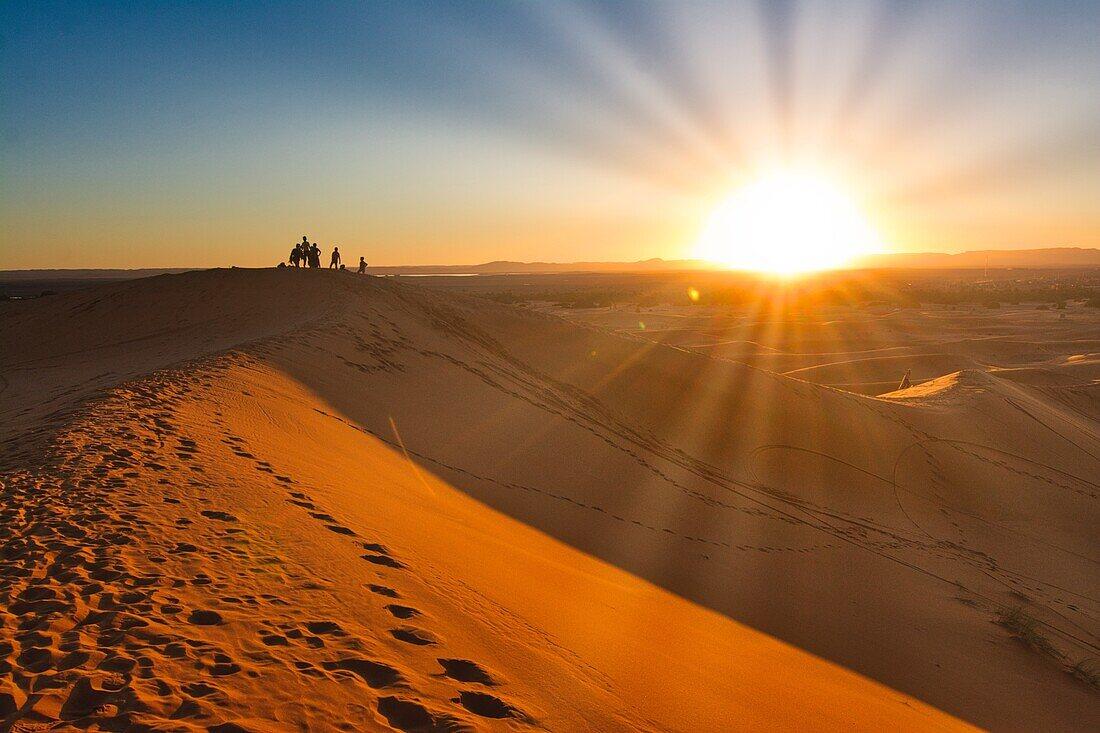 Menschen auf einer Düne bei Sonnenuntergang, Dünengebiet Erg Chebbi, Tafilalet,  Marokko