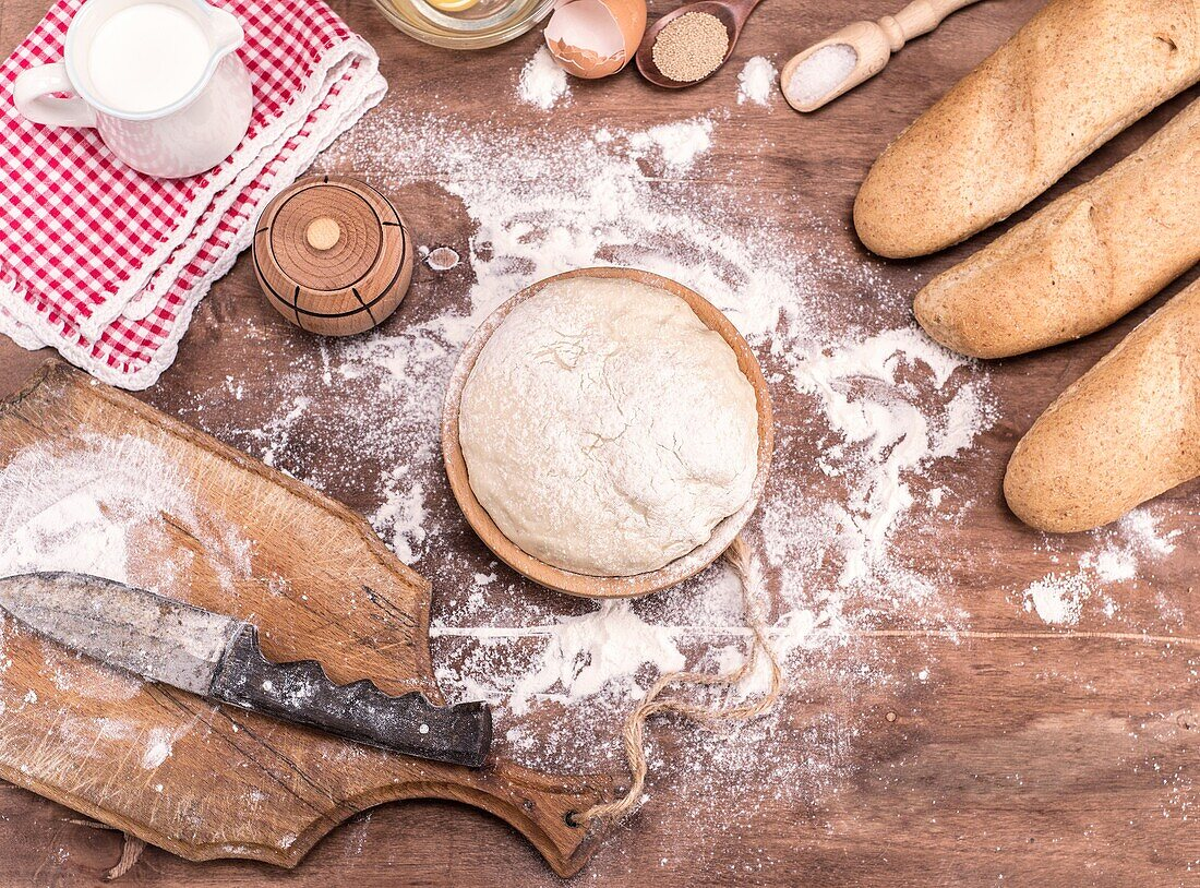Wheat yeast dough for bread and rolls in a wooden bowl on a table in the middle of the ingredients, top view.