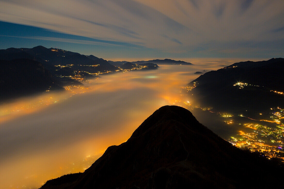 Fog bank illuminated from the lights of the cities below viewed from the top of Barro mount, Barro mount Regional Park, Lecco province, Lombardy, Italy