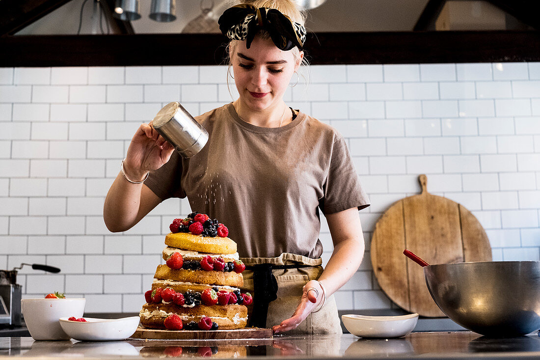 A cook working in a commercial kitchen sprinking icing sugar over a layered cake with fresh fruit.