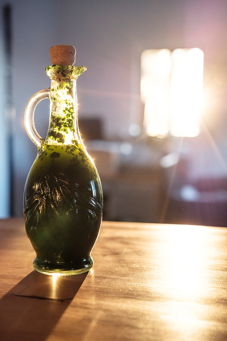 A bottle of wild garlic oil on the kitchen counter in the morning sun, Berg am Starnberger See, Bavaria, Germany.