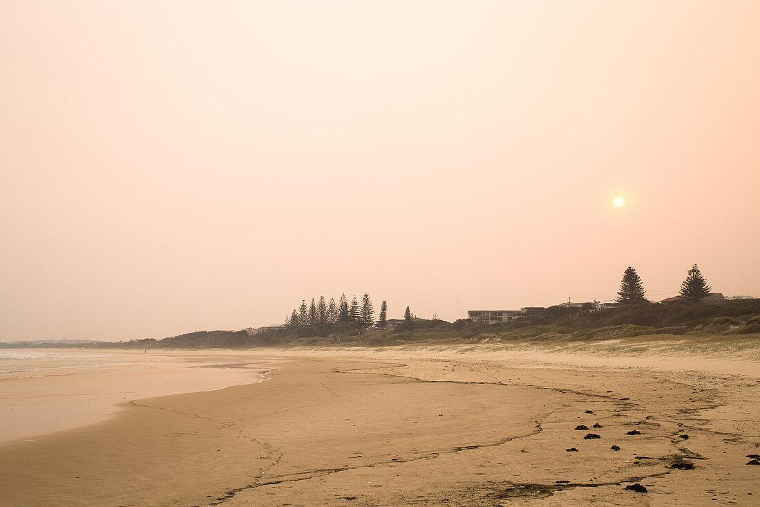 Buschfeuer färben den Himmel über Yamba rot im November, New South Wales, Australien