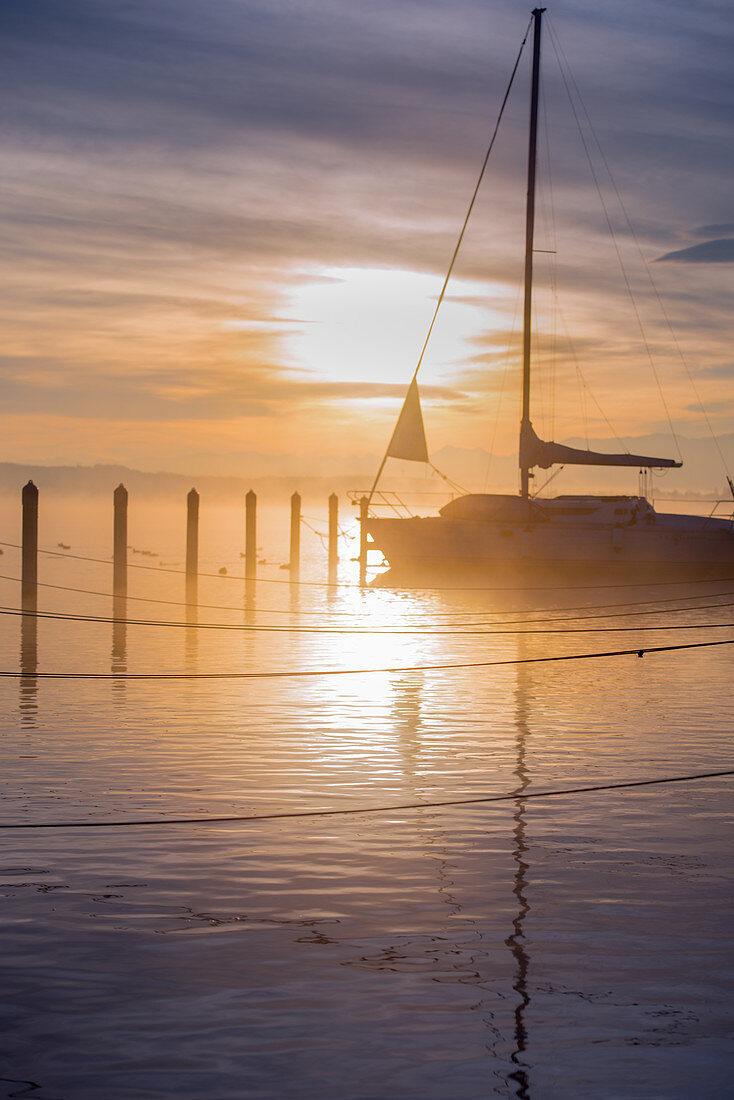 Boot im Nebel bei Sonnenaufgang am Starnberger See, Bayern, Deutschland