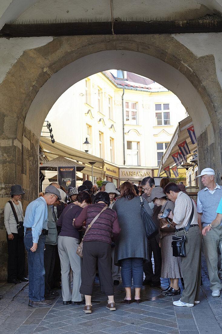 Touristengruppe unter einem Torbogen in der Innenstadt Bratislavas, Slowakei