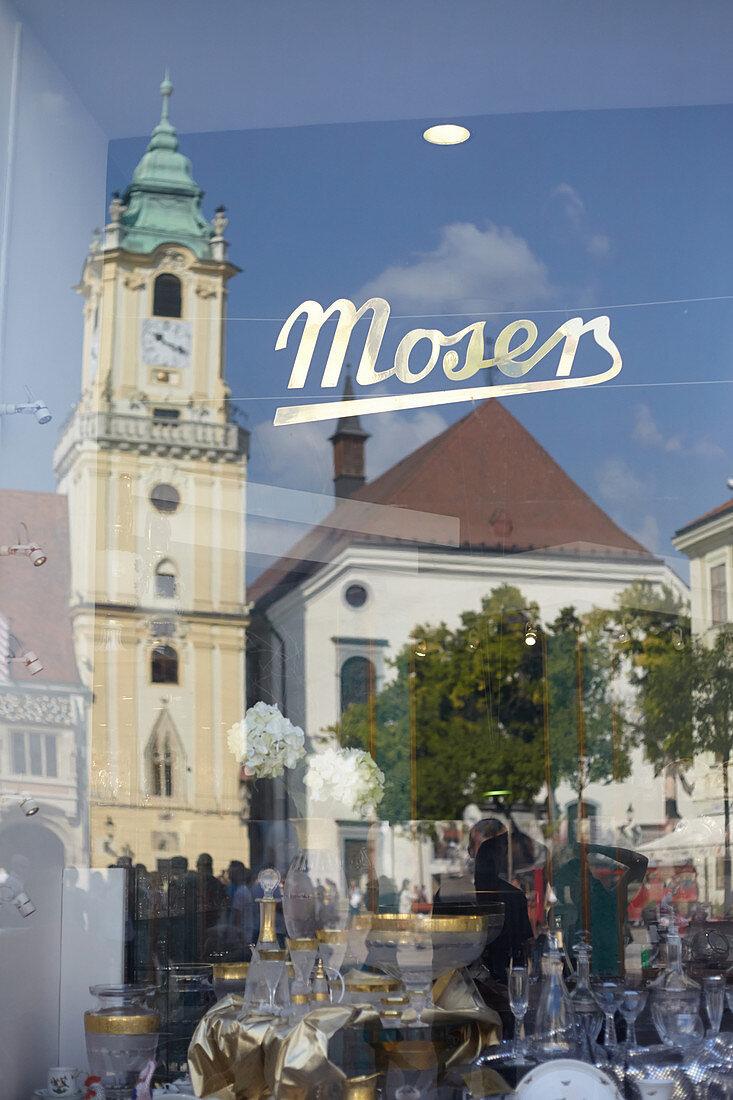Spiegelung des alten Rathauses in der Scheibe eines Einrichtungsgeschäftes auf dem Primatialplatz in Bratislava, Slowakei
