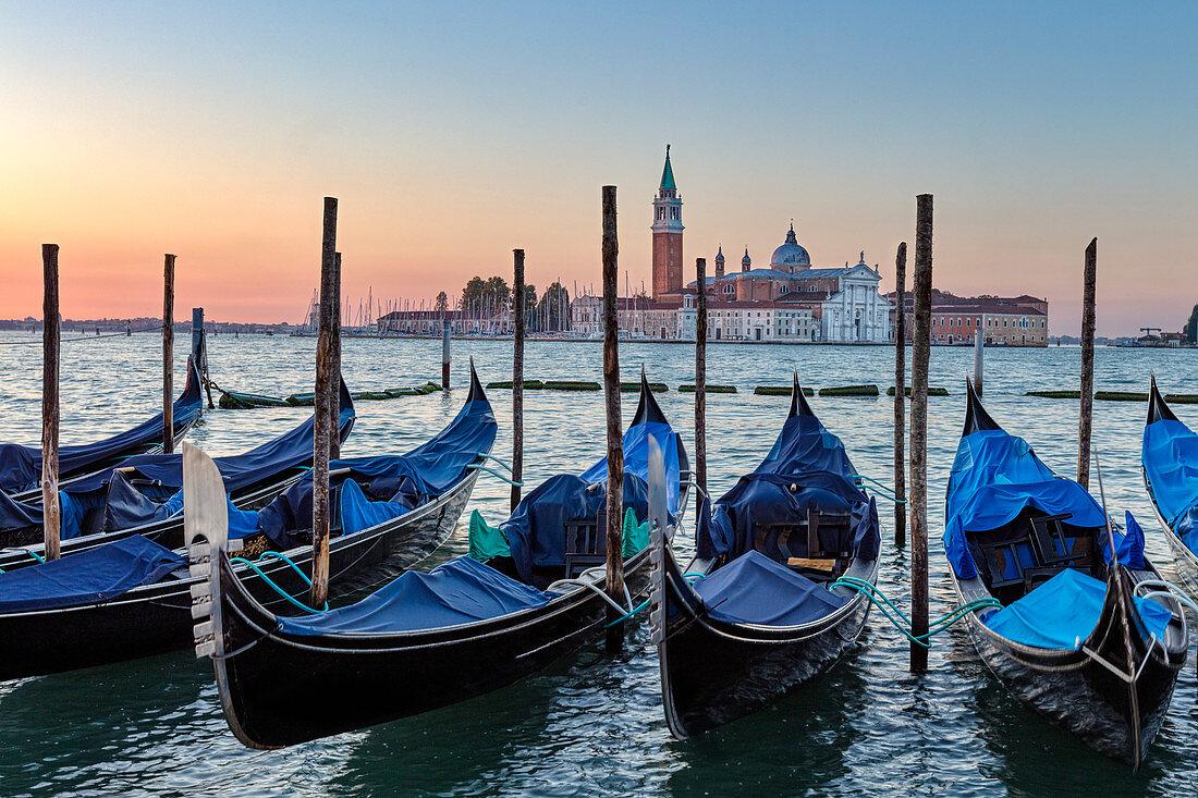 Resting gondolas in the morning Riva degli Schiavoni with San Giorgio in the background in Venice, Veneto, Italy