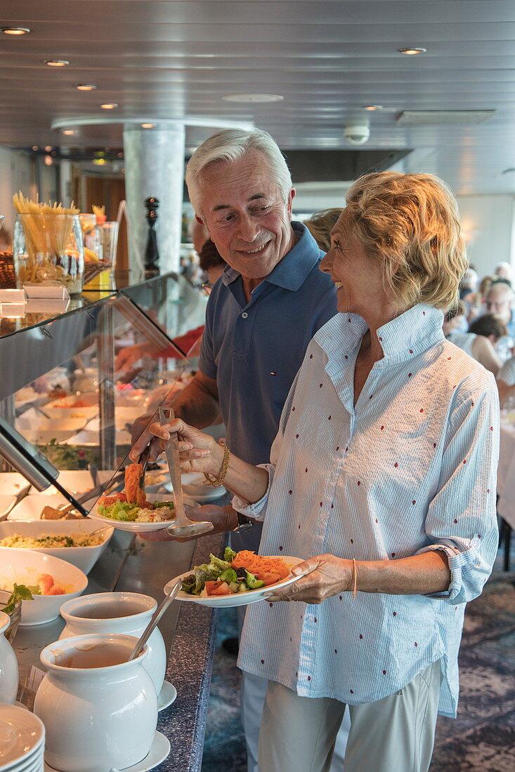 Paar am Mittagsbuffet im Panorama Restaurant an Bord von Flusskreuzfahrtschiff während einer Kreuzfahrt auf dem Rhein, Koblenz, Rheinland-Pfalz, Deutschland, Europa