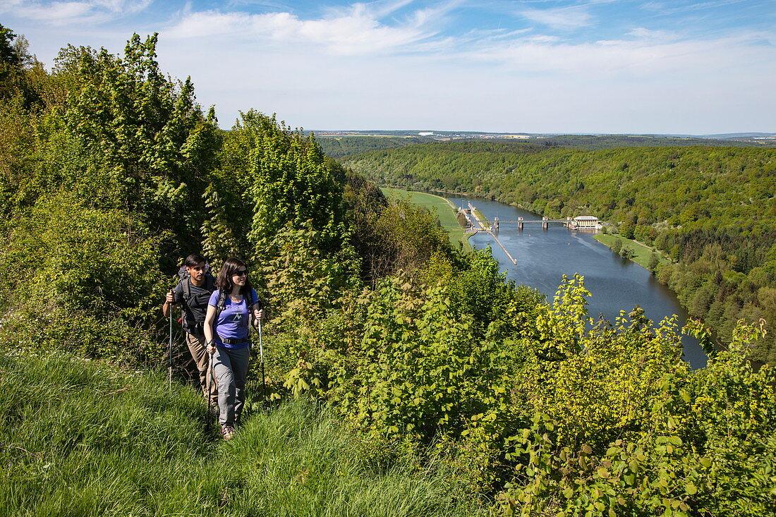 Paar wandert entlang einem Hügel oberhalb vom Main mit Blick auf die Schleuse Eichel, Wertheim, Spessart-Mainland, Franken, Baden-Württemberg, Deutschland, Europa