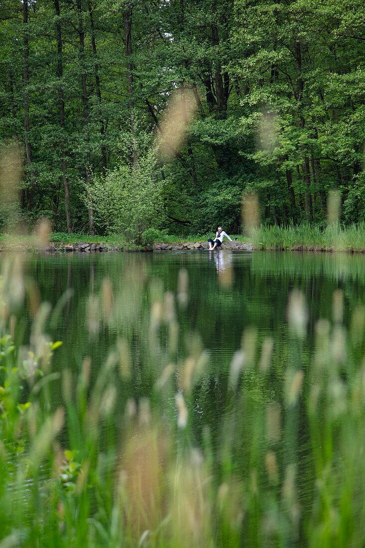 Mann entspannt am Ufer von Teich mit Gräsern im Vordergrund, Kleinostheim, Spessart-Mainland, Franken, Bayern, Deutschland, Europa