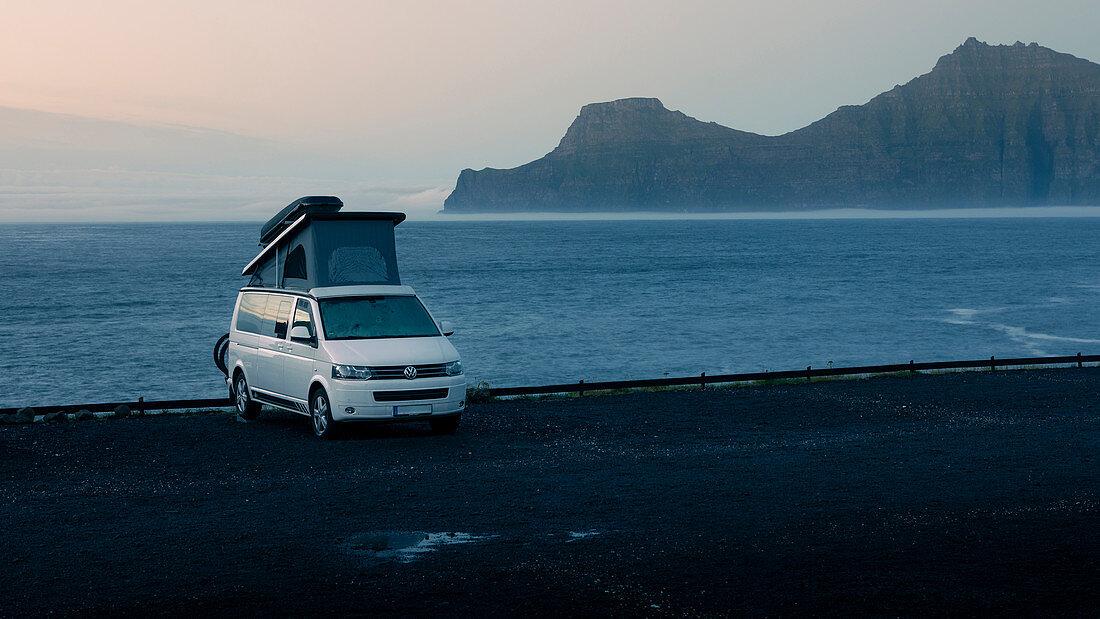 Weißer VW Campingbus mit Aufstelldach in Gjogv auf Eysturoy am Meer, Blick auf Insel Kalsoy bei Sonnenuntergang, Färöer Inseln