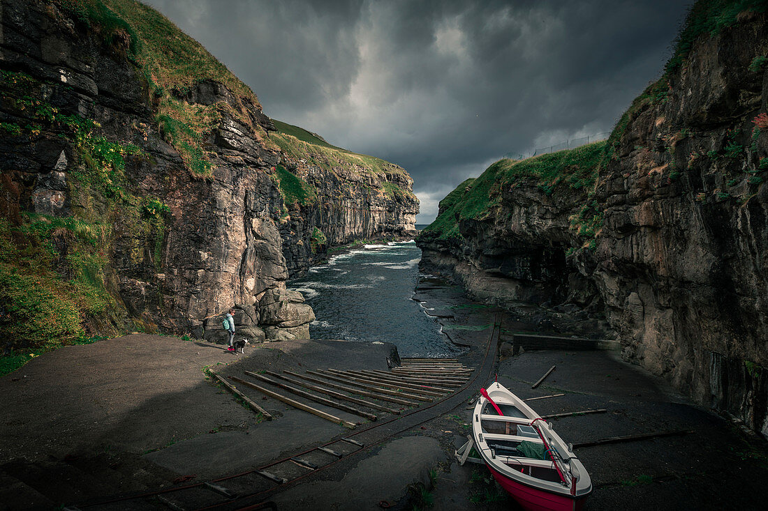 Schlucht im Dorf Gjogv auf Eysturoy, mit Boot und Frau, Färöer Inseln