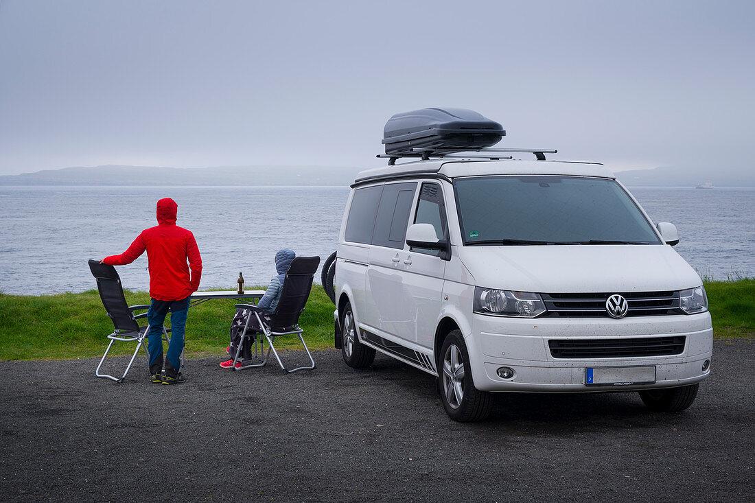 Mann und Frau mit Tisch und Campingstühlen vor Campervan am Meer auf den Färöer Inseln