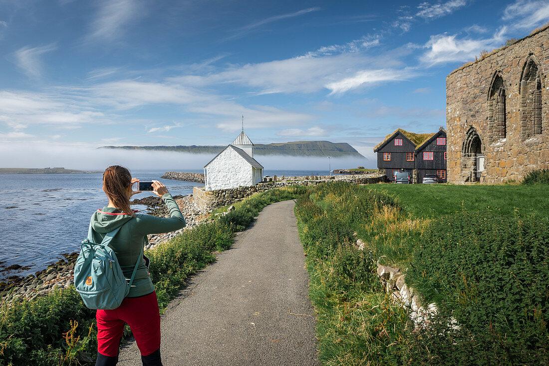 Frau fotografiert Kirche und Ruine im Dorf Kirkjubøur auf Streymoy, Färöer Inseln