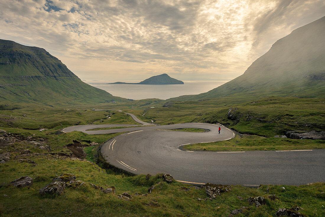 Mann auf der kurvigen Straße nach Norðradalur auf Streymoy, Färöer Inseln
