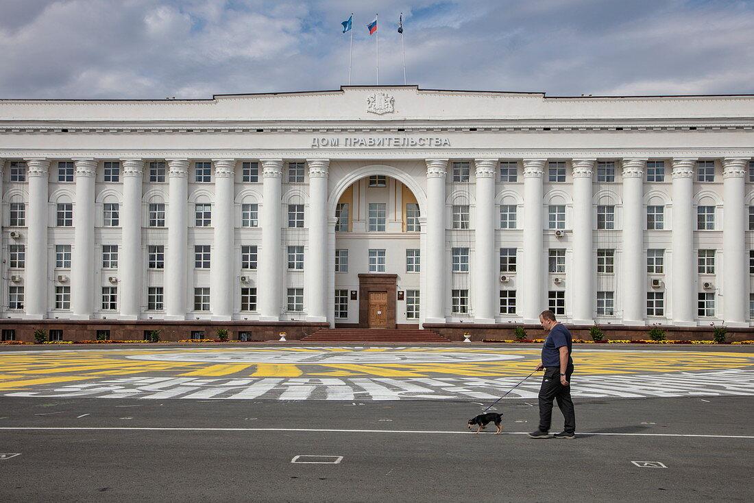 Man and dog walking in Lenin Square, Ulyanovsk, Ulyanovsk District, Russia, Europe
