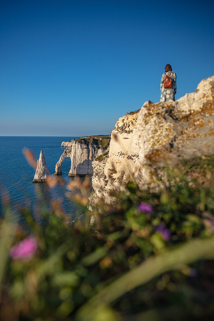 A woman sits on the Alabaster Coast and looks at the Porte d'Aval rock arch and the Aiuille rock needle near Étretat, Normandy, France.