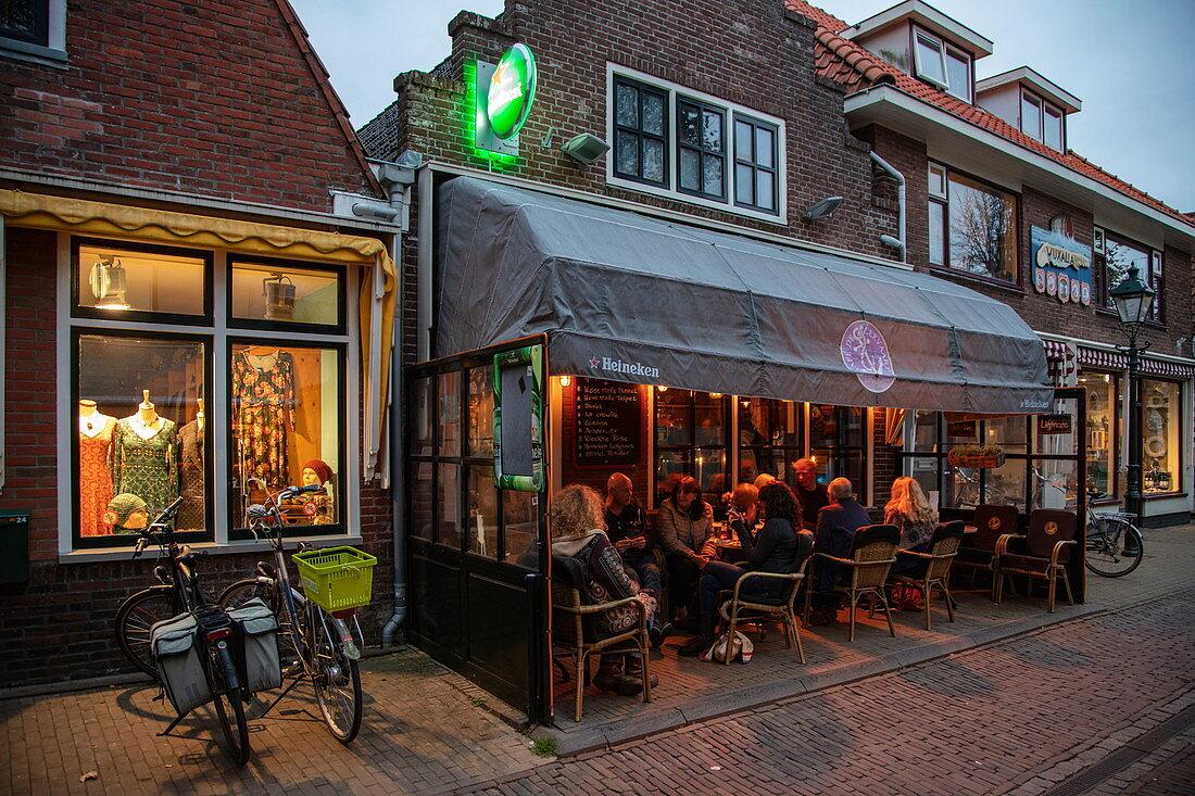 People sitting outside and enjoying beer in Cafe de Zeevaart at dusk, West Terschelling, Terschelling, West Frisian Islands, Friesland, Netherlands, Europe