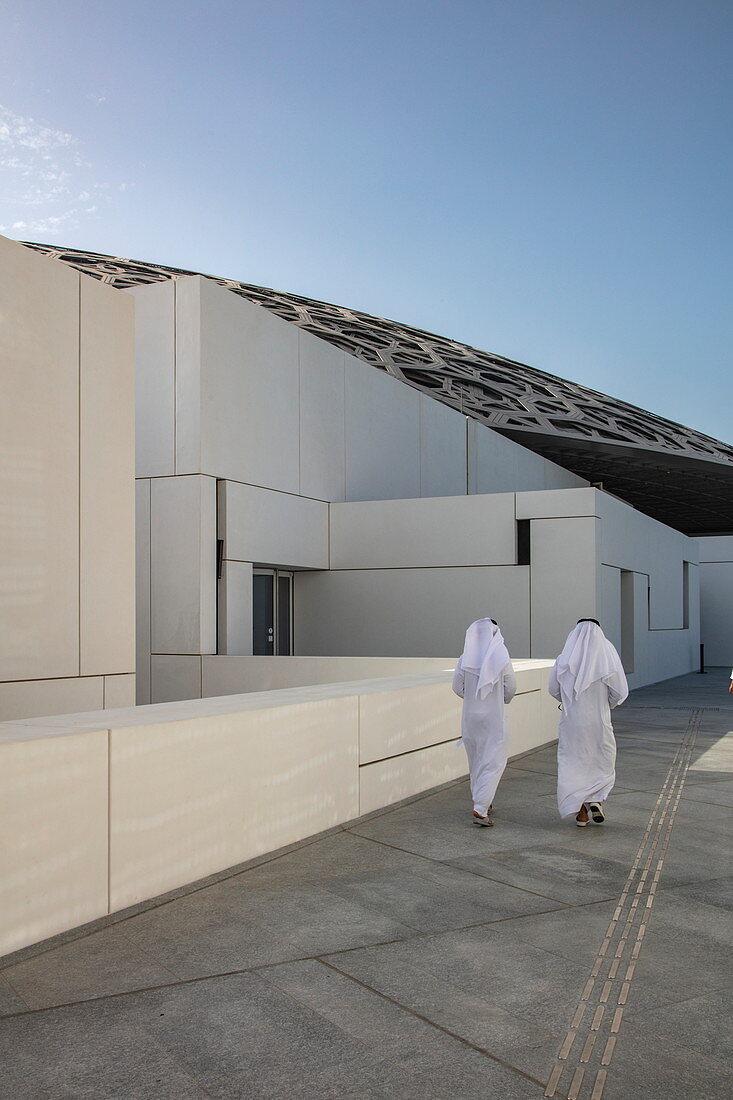 Two Arab men walk running along path outside the Louvre Abu Dhabi Museum, Abu Dhabi, Abu Dhabi, United Arab Emirates, Middle East