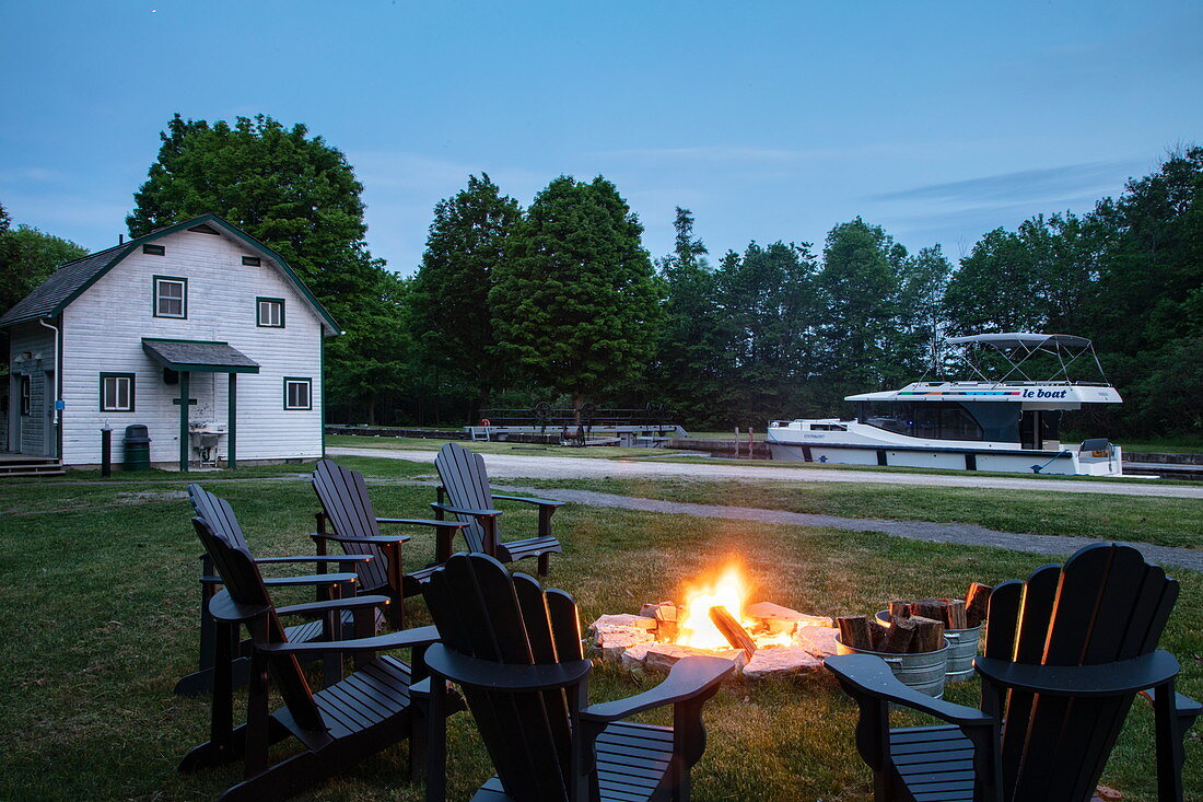 Chairs surround campfires at Parks Canada Campground at Beveridge Locks on the Tay River with a docked Le Boat Horizon houseboat at dusk, near Lower Rideau Lake, Ontario, Canada, North America