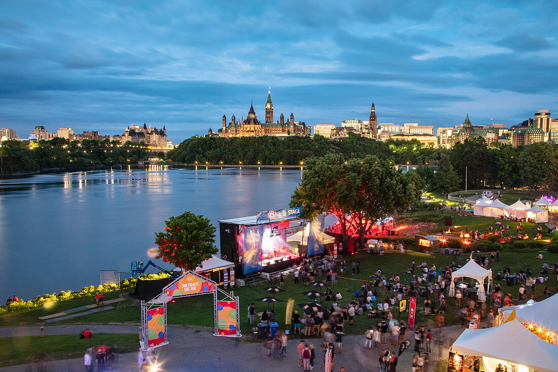 People enjoying music and beer at the Gatineau Festibiere beer festival overlooking the city skyline at dusk, Ottawa, Ontario, Canada, North America