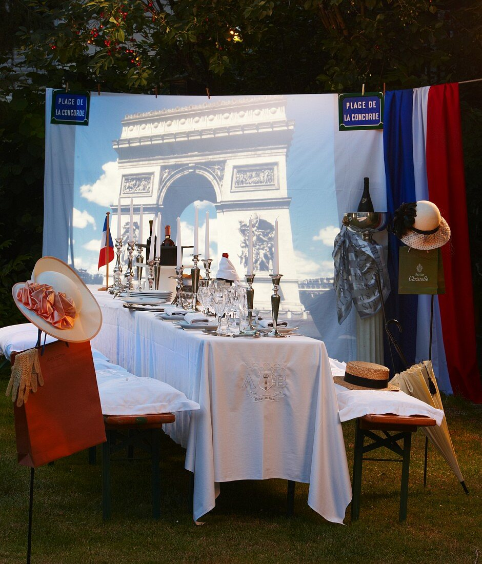 A festively laid table for a French-themed party in the open air