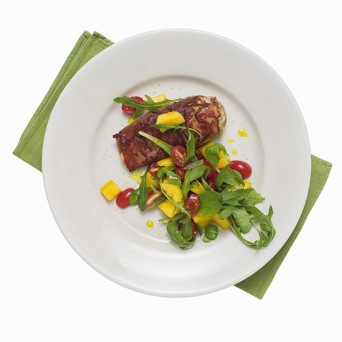 Bacon-wrapped chicken breast with tomato and mango salad