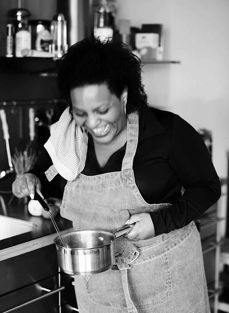 Laughing woman stirring a pan