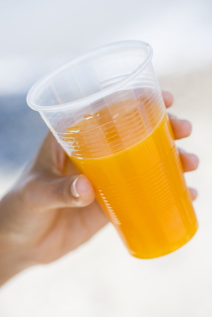 Hand holding plastic cup of orange juice