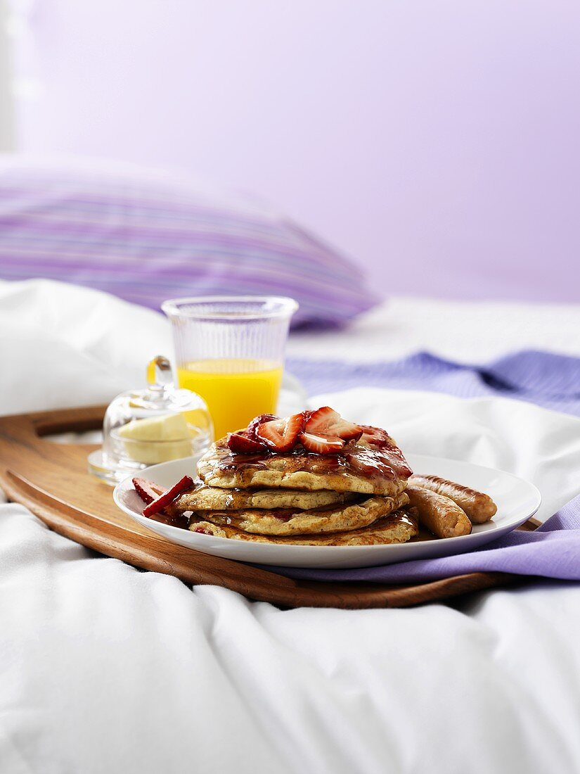 Breakfast in bed (orange juice, pancakes with berries and sausages)