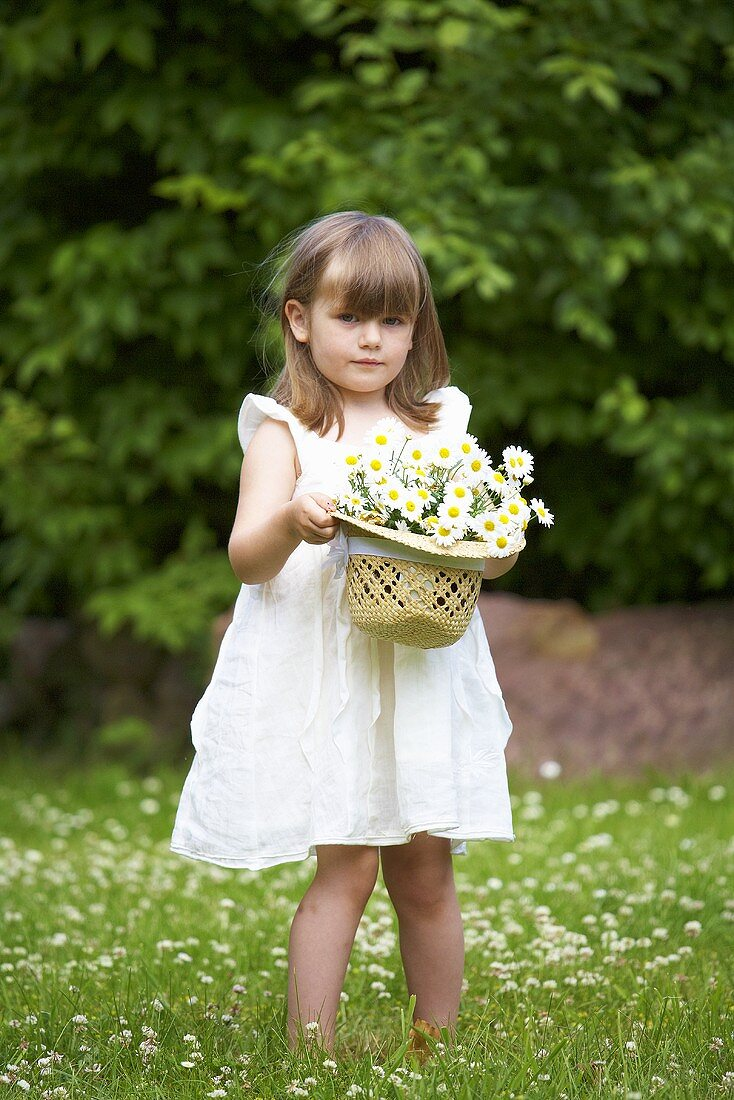 A little girl holding a straw hat filled with daises