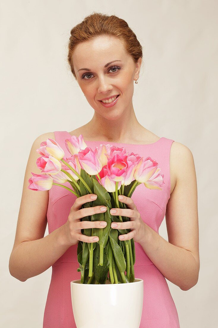 A woman with a bunch of pink tulips