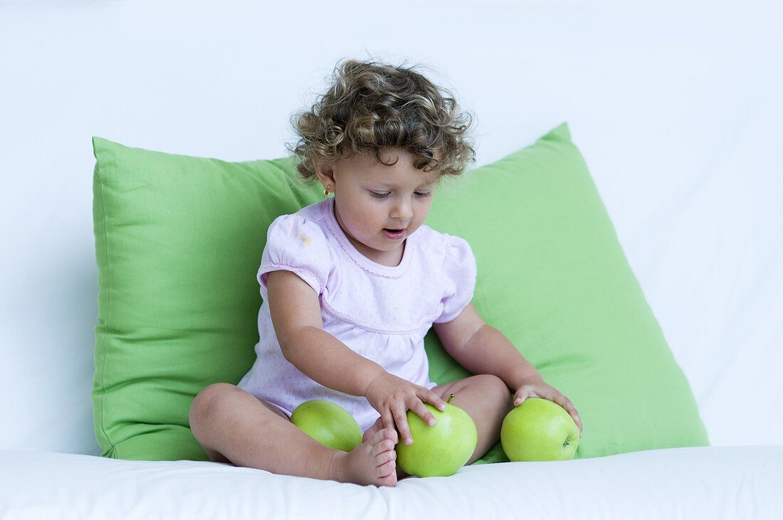A little girl playing with green apples on a sofa